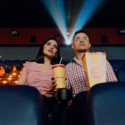 Woman and man at movie theater. Telecoil is often an option in public venues.